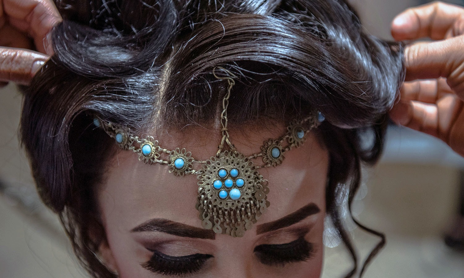 Afghan beauticians affix jewellery to the hairstyle of a bride ahead of her wedding party at a beauty parlour in Kabul. ─AFP