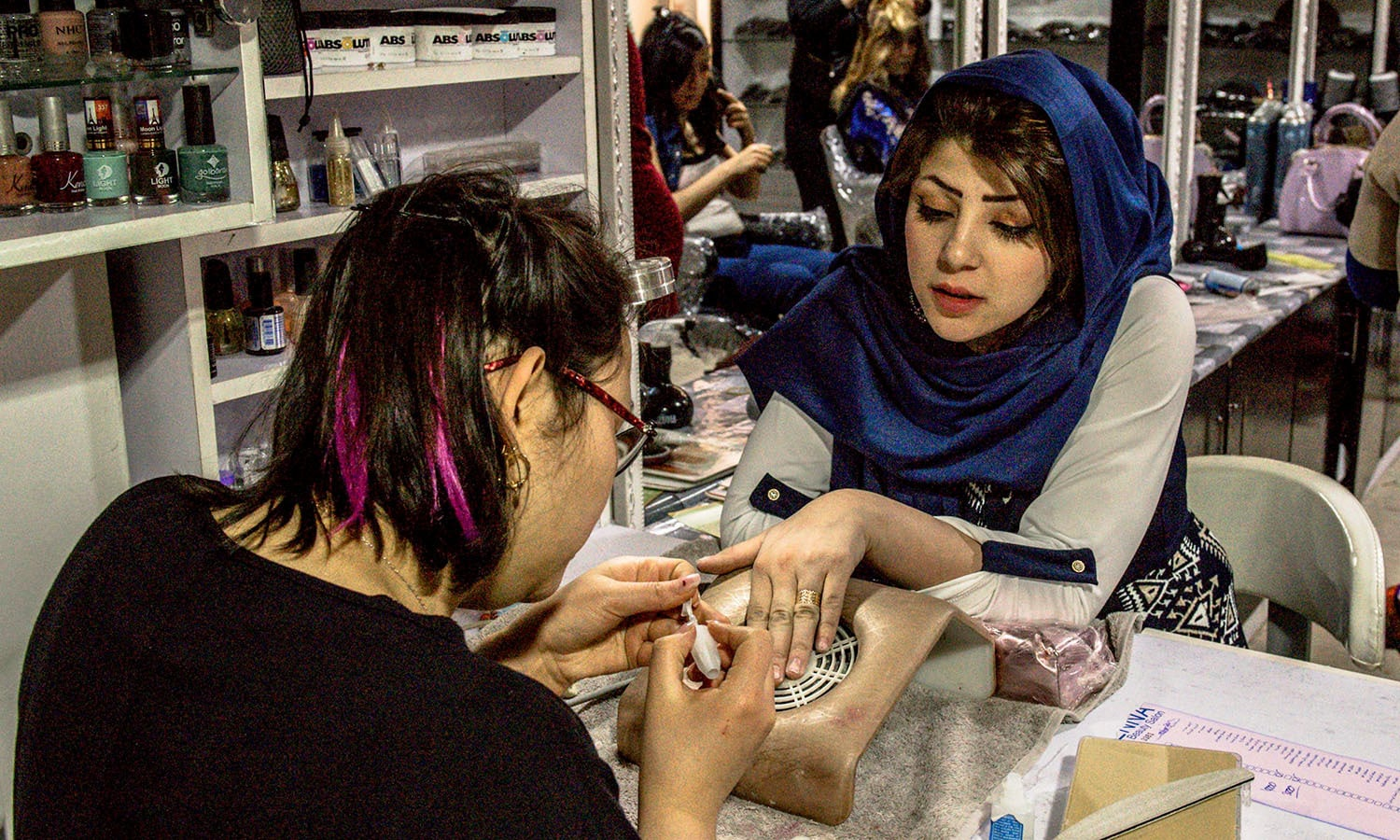 Afghan beautician Sadaf, 17, and who has worked at the beauty parlour for one year, applies false nails at the start of a manicure for a wedding party guest at a beauty parlour in Kabul. ─AFP