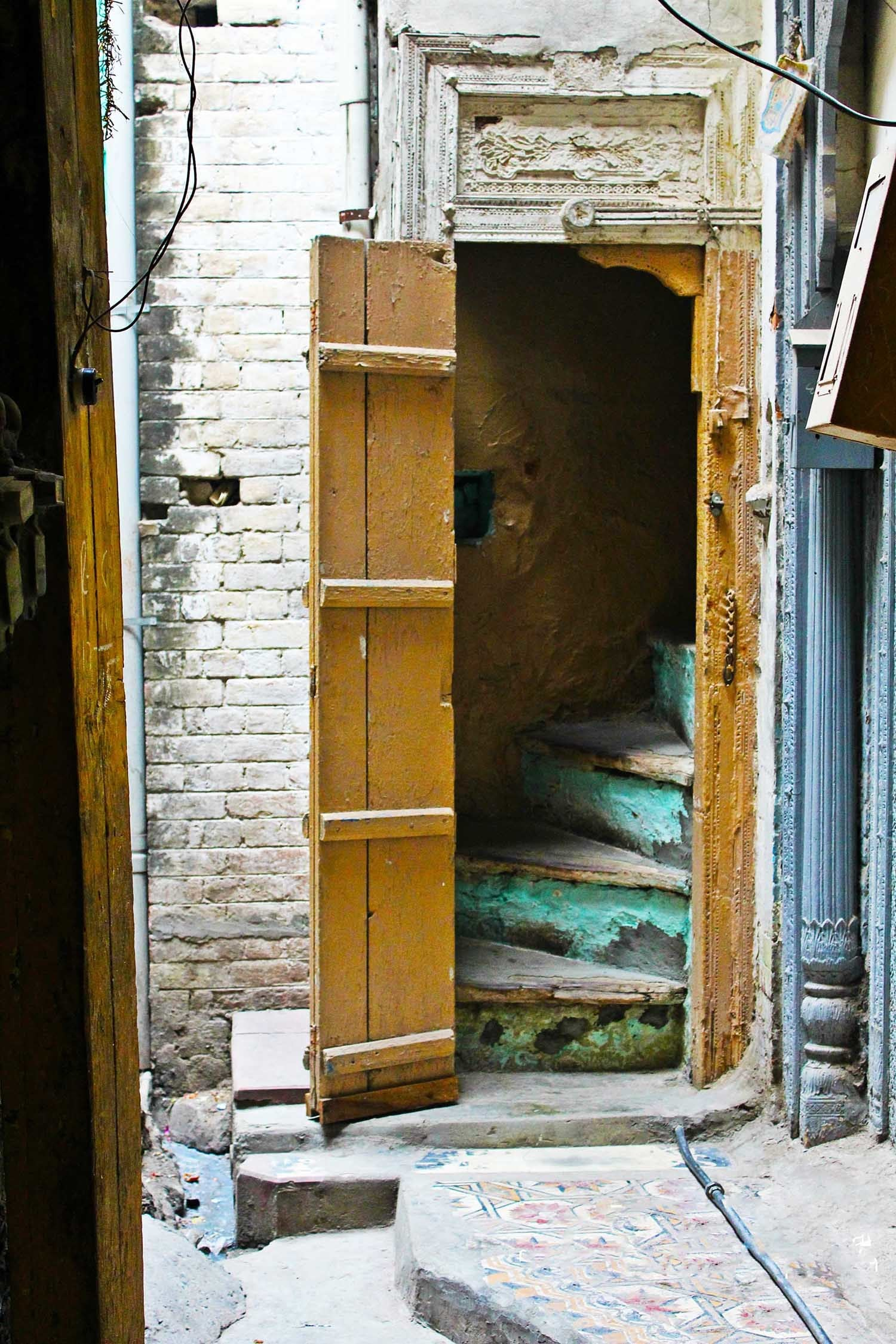 A narrow, winding stair case leading up to a preserved *haveli*, which still has traces of its magnificent architecture from 1893.
