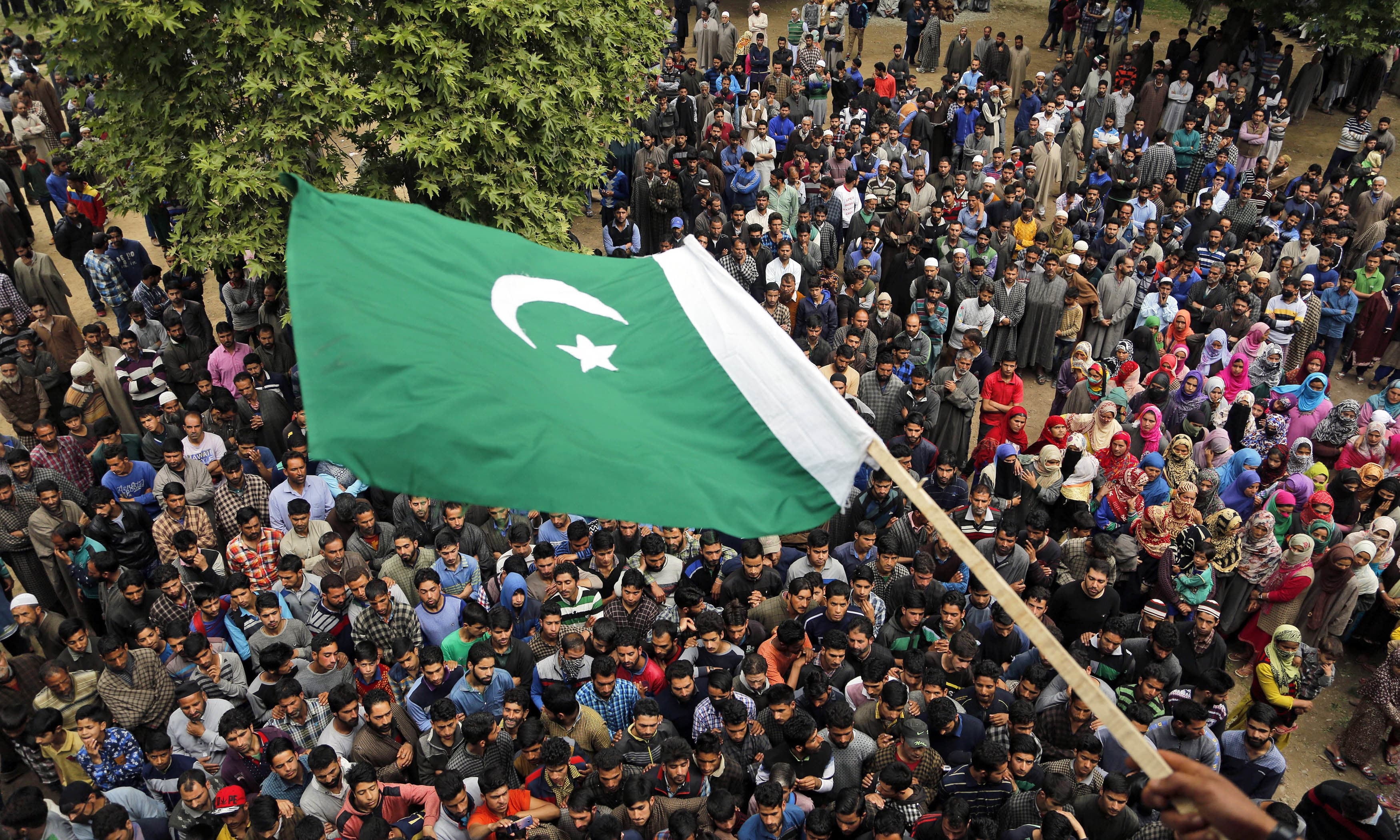 A villager waves a Pakistani flag during the funeral of Fayaz Ahamed in Kaimuh, south of Srinagar. —AP