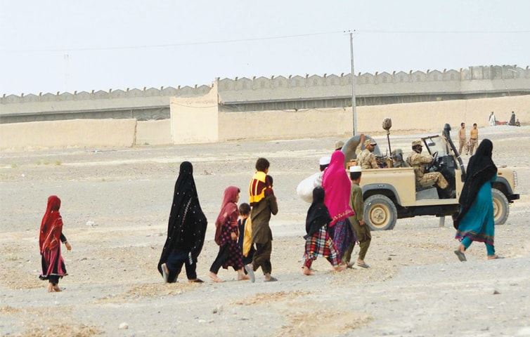A FAMILY leaves Chaman in search of safety on Sunday as Pakistani troops on a jeep pass by.—PPI