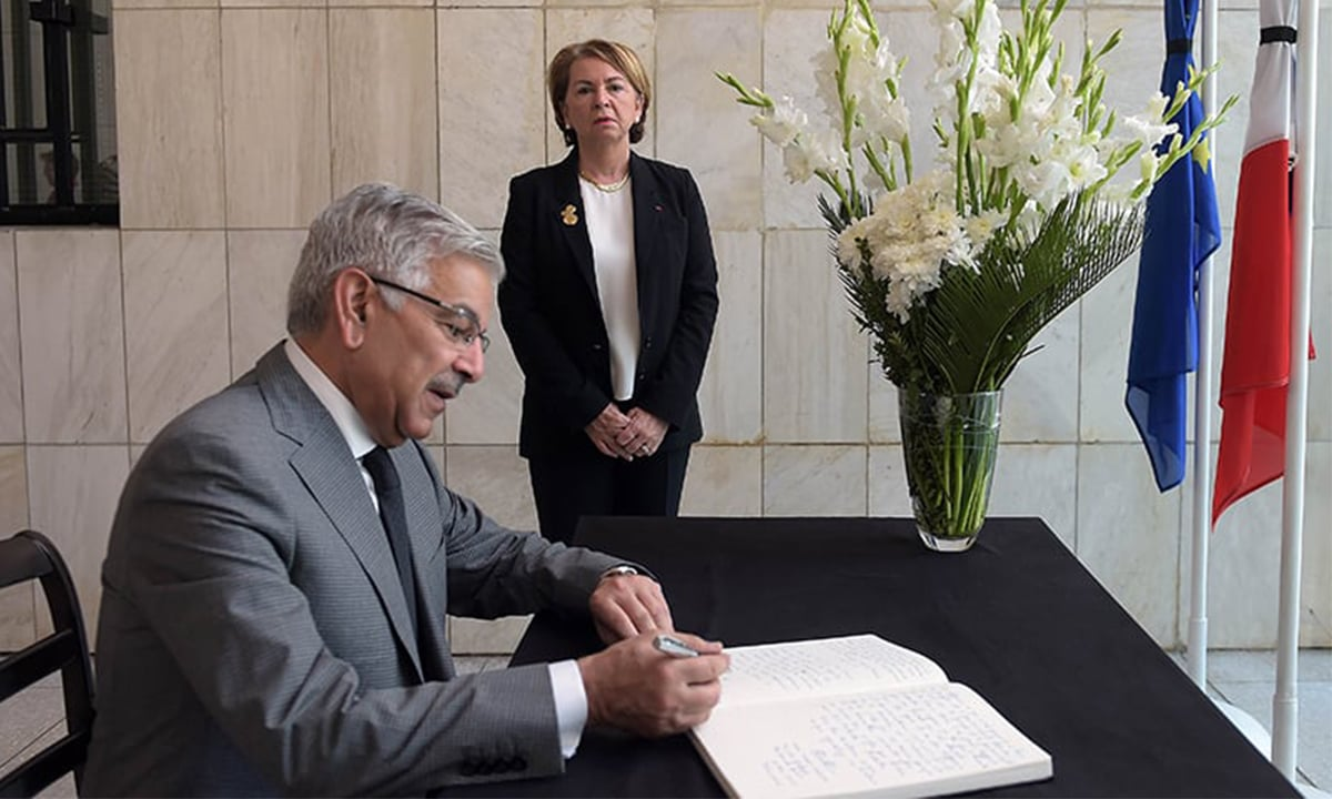 Khawaja Asif writes a message in a condolence book at the French Embassy in Islamabad | AFP