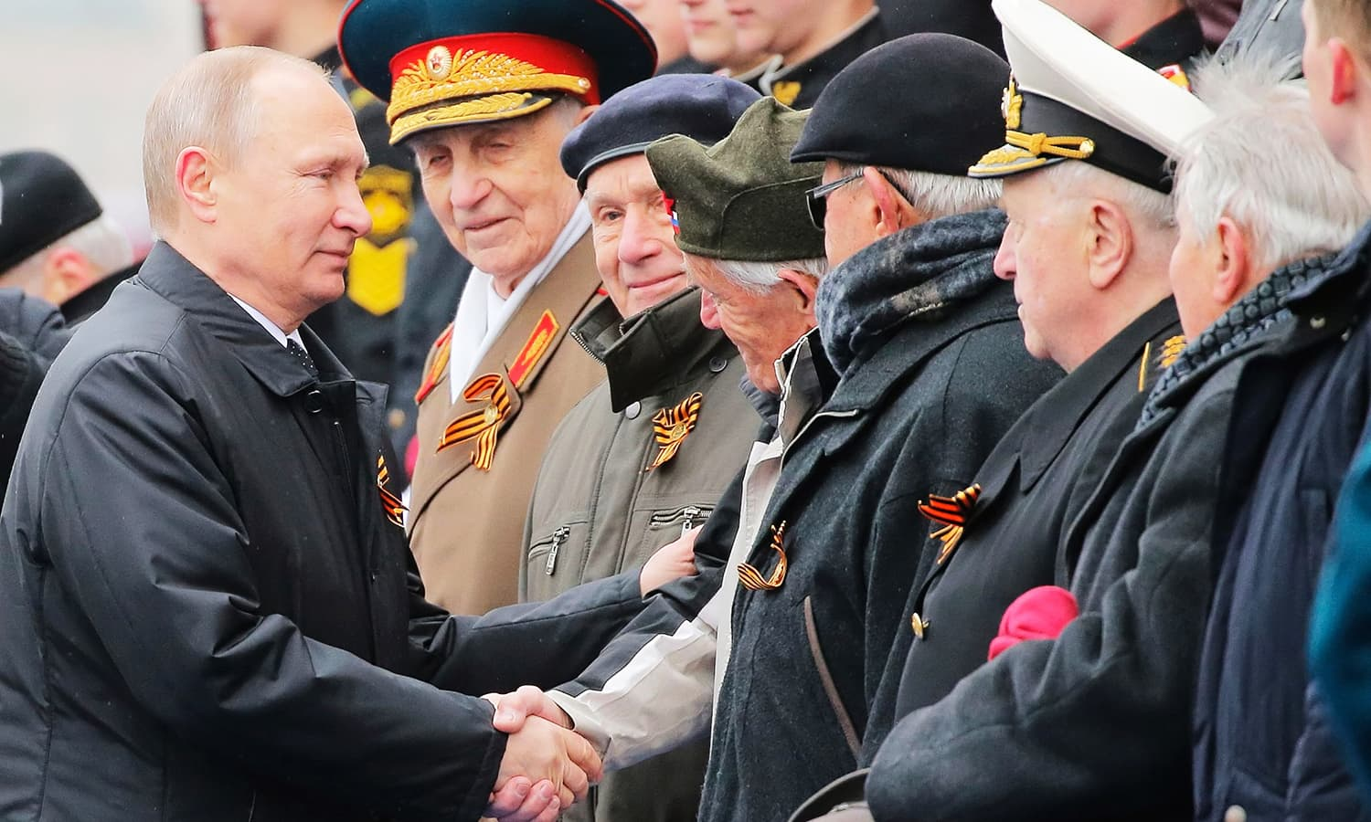 President Vladimir Putin shakes hands with veterans after the Victory Day military parade. -AFP