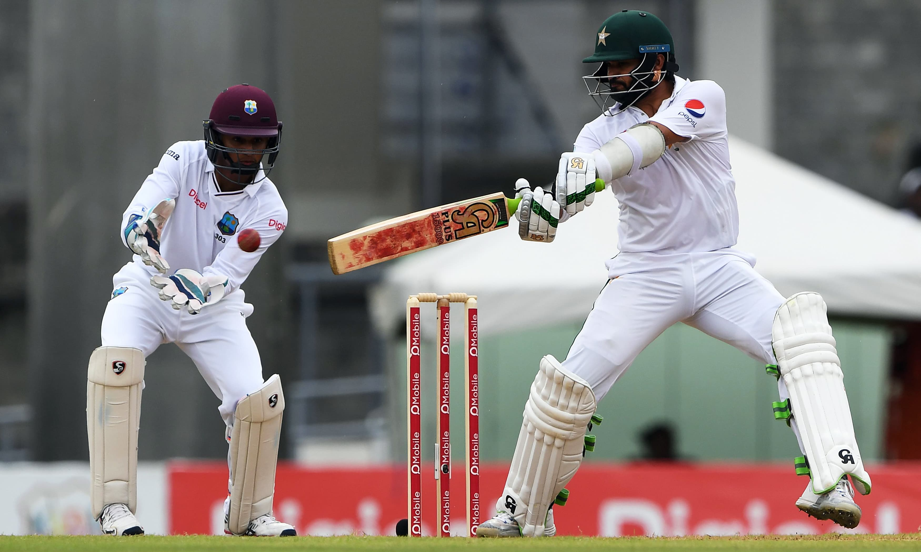 Azhar Ali plays a cover shot as Shai Hope looks on. —AFP