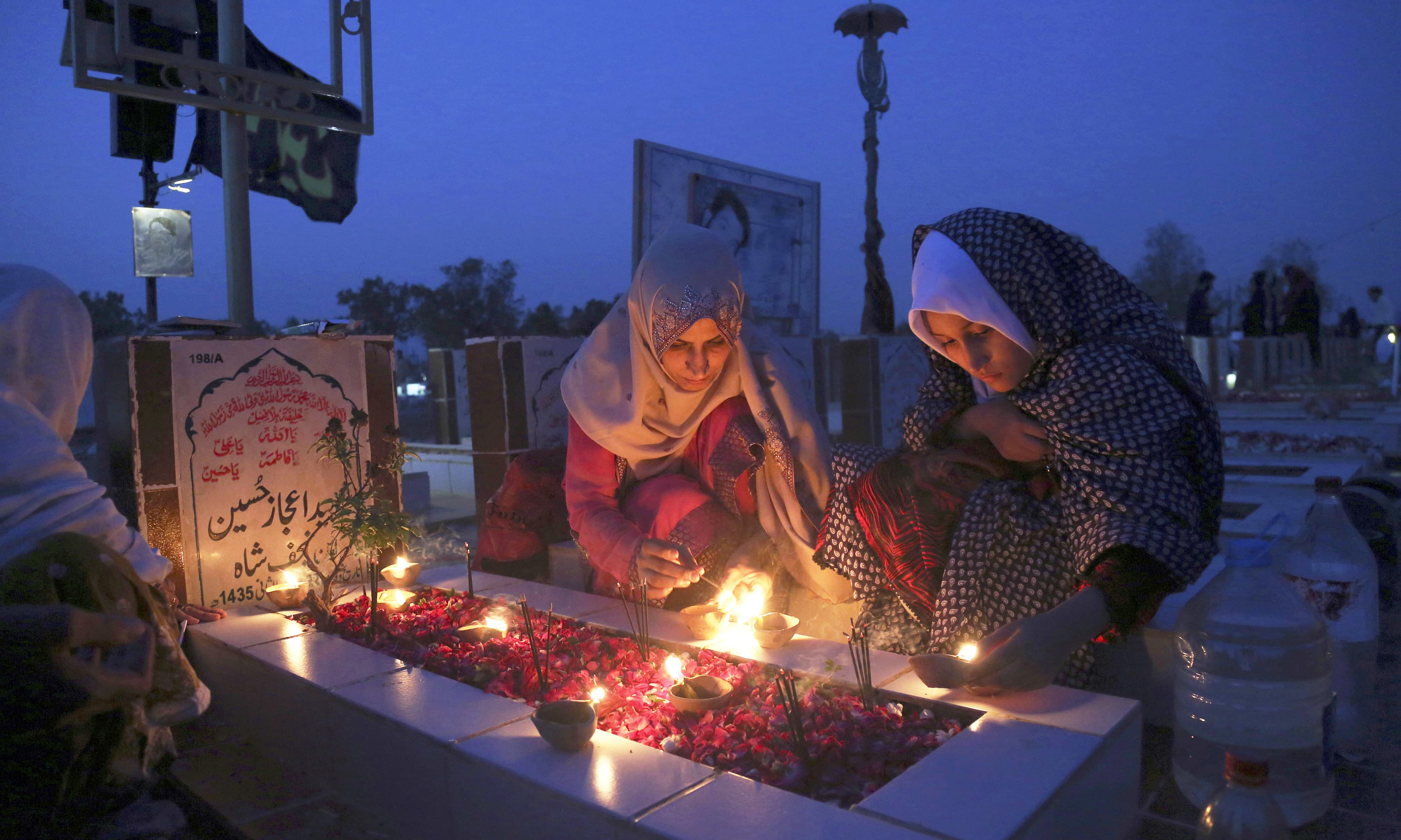Family members light lamps and pray at a grave of their relative. —AP
