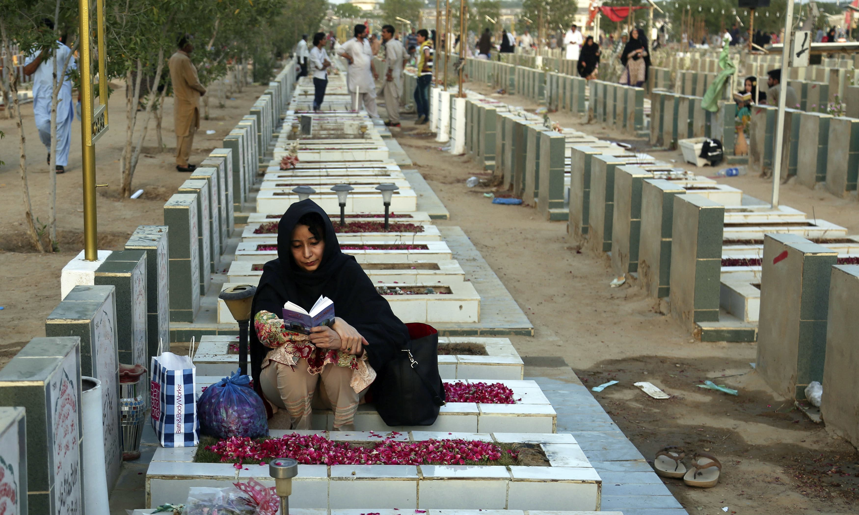A woman recites the holy verses besides a grave of her relative at a graveyard in Karachi. —AP
