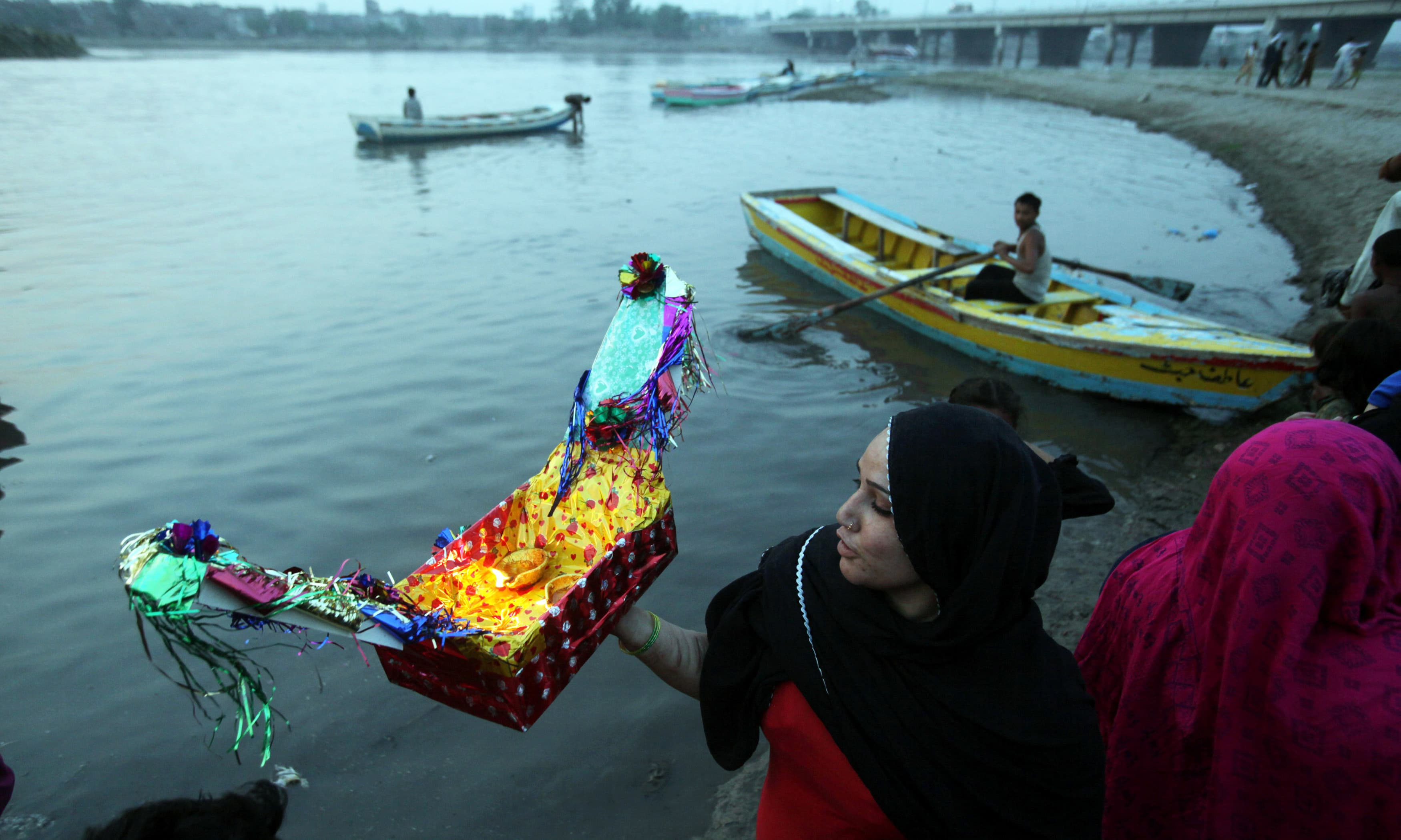 Women release oil lamps and candles in the water of Ravi river, seeking forgiveness and repentment. —Reuters