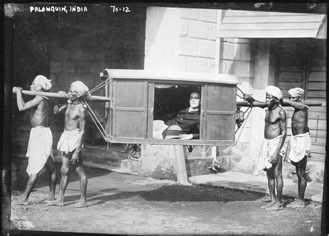 An English merchant travels comfortably in a palanquin carried by Indian locals | Library of Congress