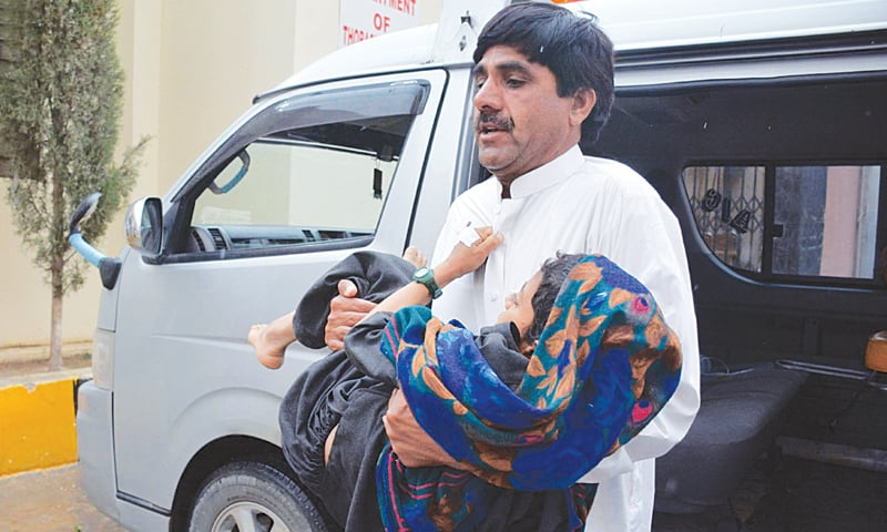 QUETTA: A man carries a child injured in the bomb blast in Mastung on Friday.—INP