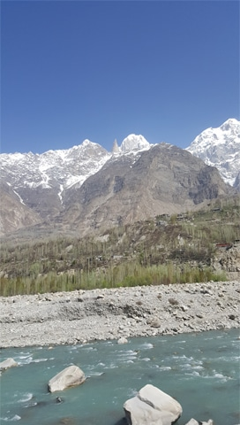 Hunza River flows in the foothills of mighty mountains