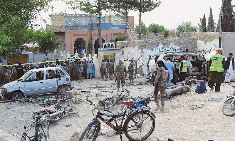 Security officials examine the site of the bomb attack in Mastung district on Friday. Officials of the bomb disposal squad said it was a suicide attack.— AFP
