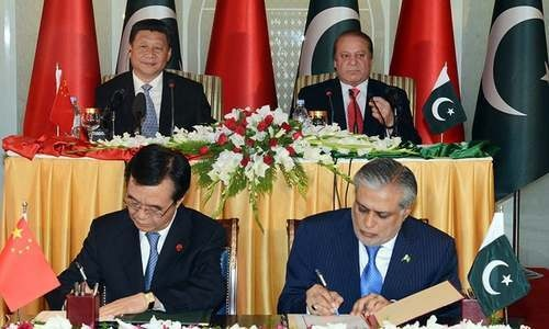 President Xi Jinping and Prime Minister Nawaz Sharif overlook the signing of agreements between the two countries. — AFP