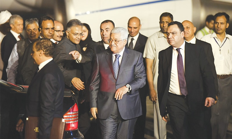 President Mahmud Abbas (centre) walks with officials after arriving in New Dehli on Sunday.—AFP