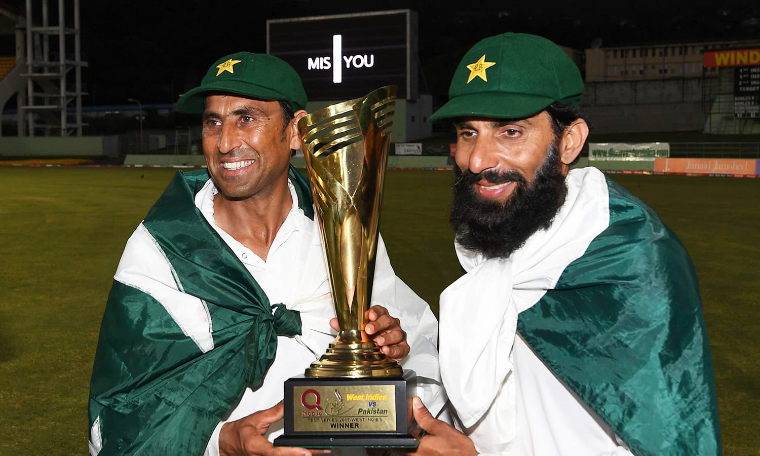 Younis and Misbah raise the victor's trophy after securing Pakistan's first-ever win at the Caribbean. — AFP