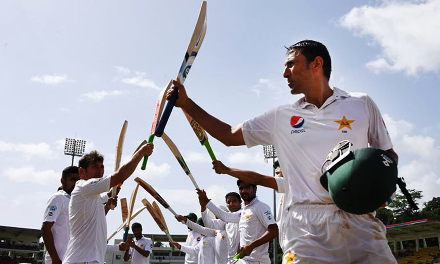 Younis raises a bat to his team mates as he walks off the pitch after his final inning. — ICC's Twitter