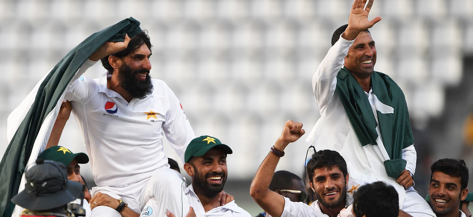 Retiring Pakistan cricket team members captain Misbah-ul-Haq (L) and Younis Khan (R) are carried by teammates as they celebrate after winning the final test match and the series 2-1 against the West Indies at the Windsor Park Stadium in Roseau, Dominica on May 14, 2017. / AFP PHOTO / Mark RALSTON — AFP or licensors