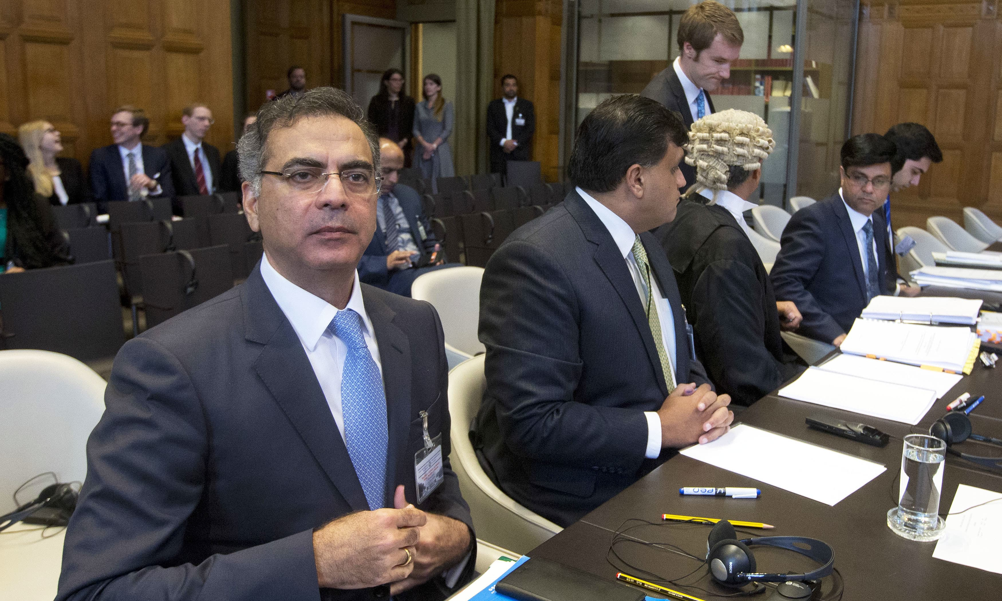 Moazzam Ahmad Khan, head of Pakistan's delegation, and members wait for judges to enter the World Court in The Hague, Netherlands. —AP