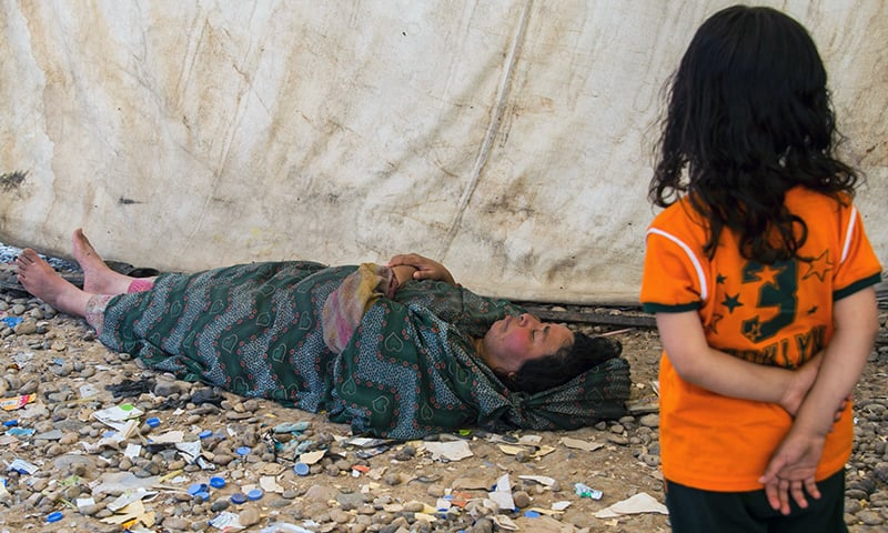 An Iraqi woman sleeps on the ground at the camp.— AFP