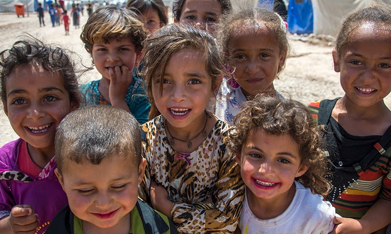 Iraqi children stand at the refugee camp in Hammam al-Alil. — AFP