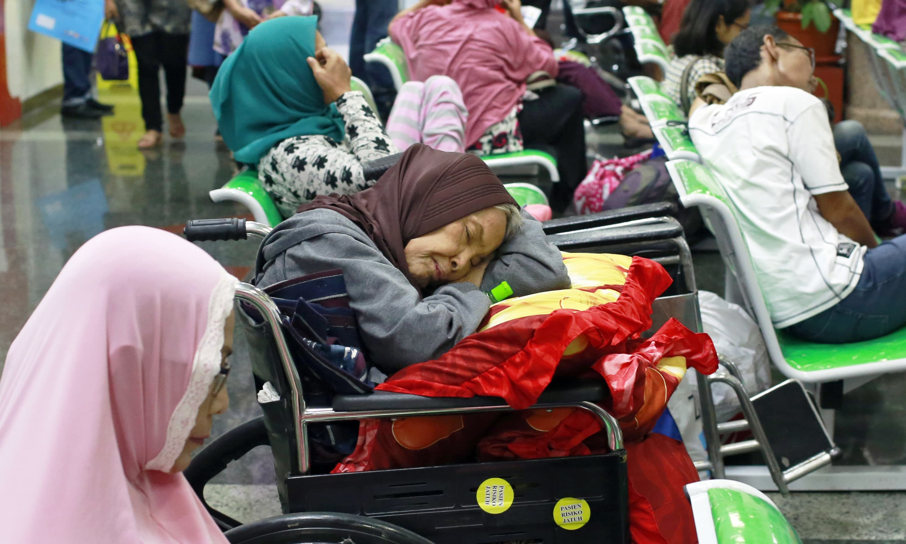 A patient takes a nap on her wheelchair as she waits with others at the registration desk at Dharmais Cancer Hospital in Jakarta. —AP