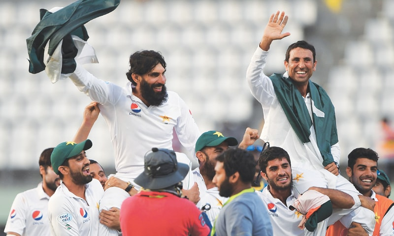 TEAM-MATES hold retiring Pakistan captain Misbah-ul-Haq (L) and legendary batsman Younis Khan on their shoulders as they celebrate winning the Test series against the West Indies at Windsor Park Stadium on Sunday.—AFP