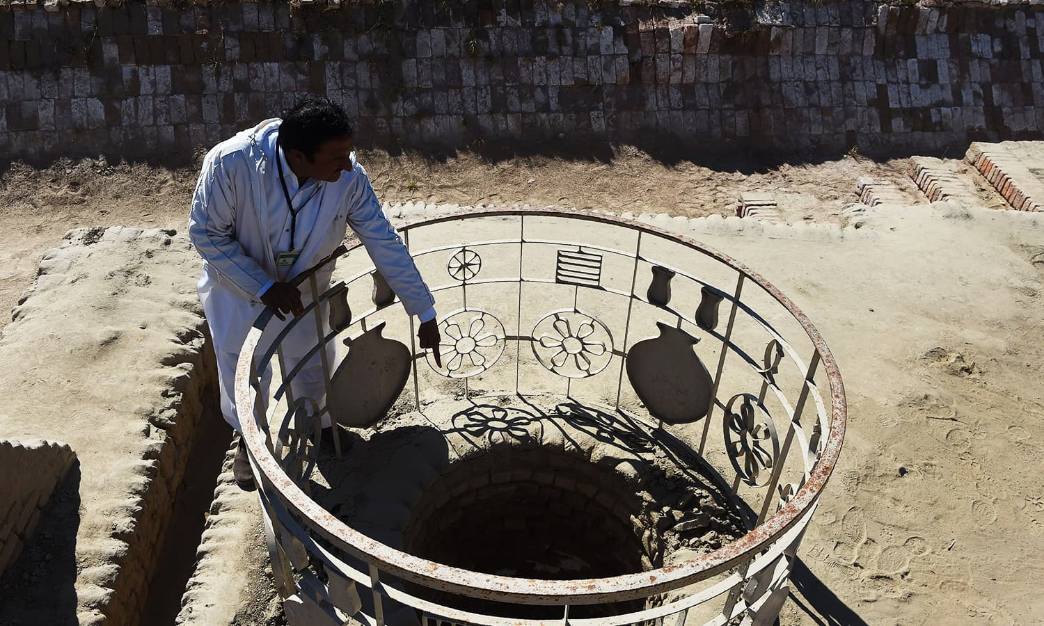 Caretaker at the UNESCO World Heritage archaeological site of Mohenjo Daro, Ismail Mugheri, points out a well at the site some 425km north of Karachi. — AFP