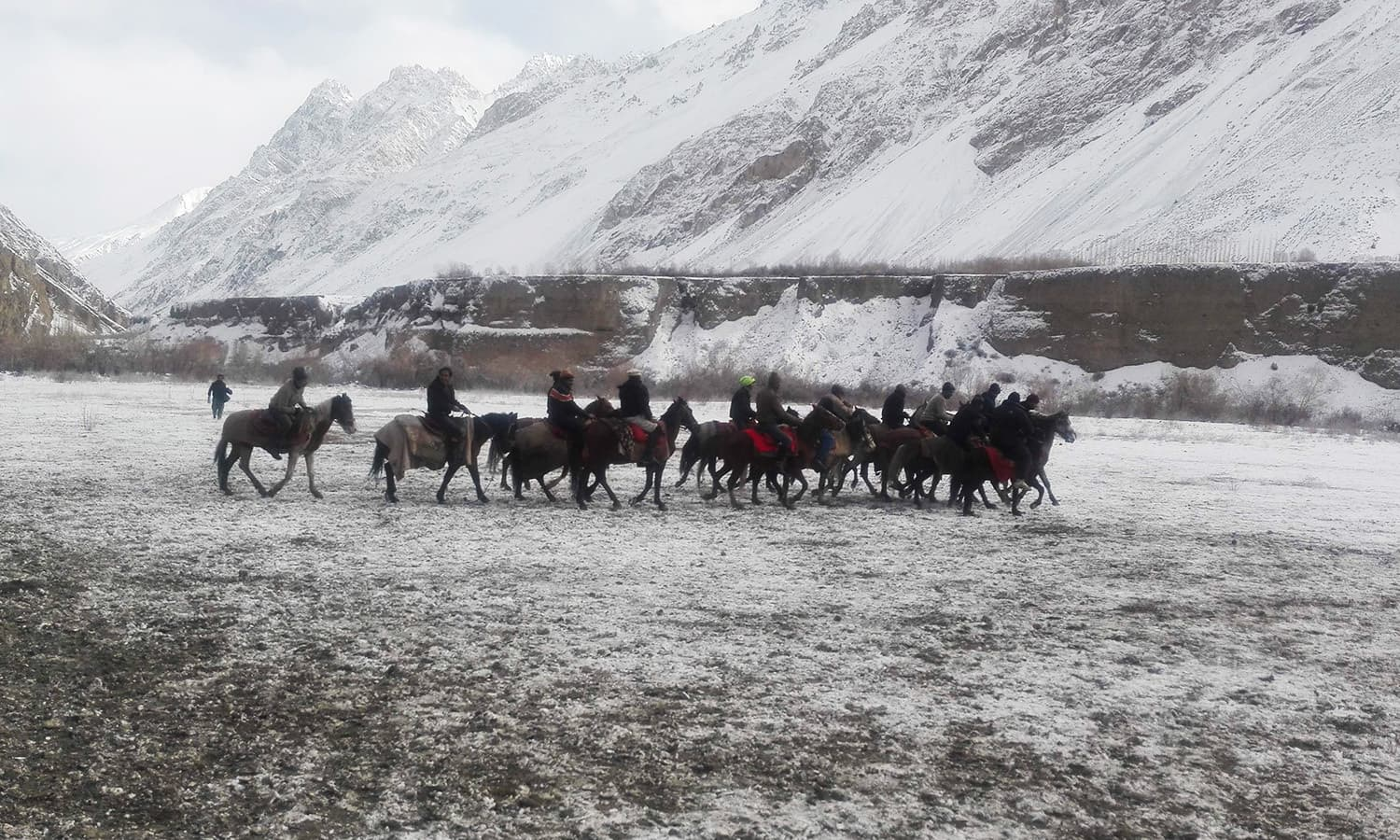 In a remote northern valley surrounded by giant ice-capped peaks, villagers gather to watch a game of Buzkashi.─AFP
