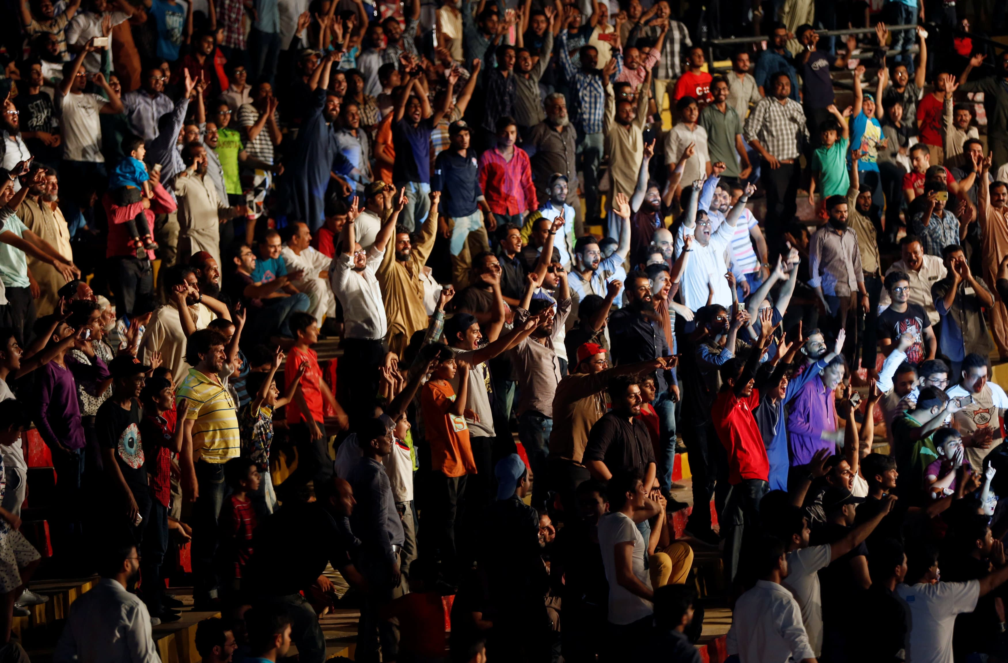 Pakistani wrestling fans react as they watch a fight during the show in Karachi.