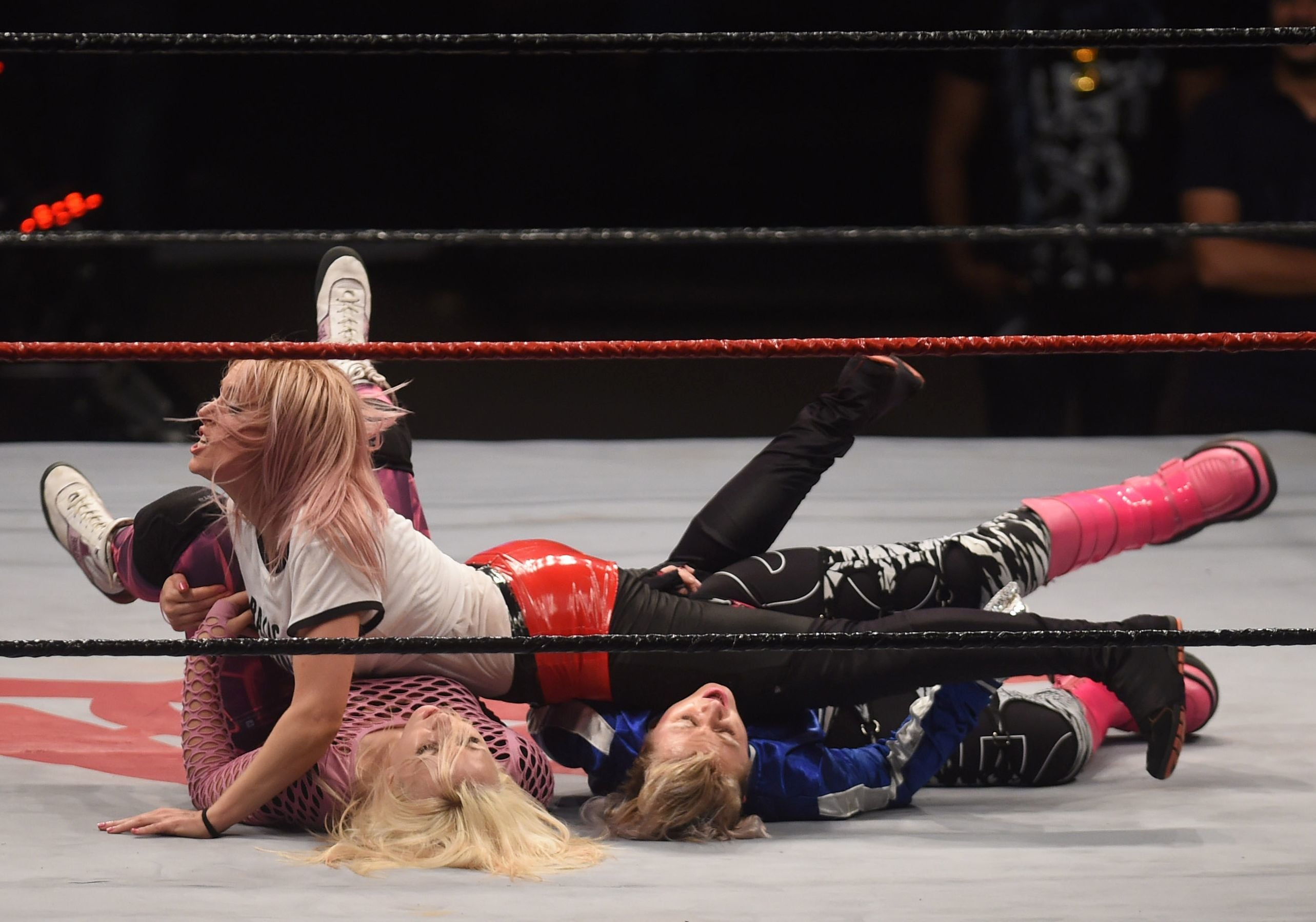 Professional wrestler Audrey Bride (top) fights with her opponents Betty Trash (L) and Angel's Bombita.