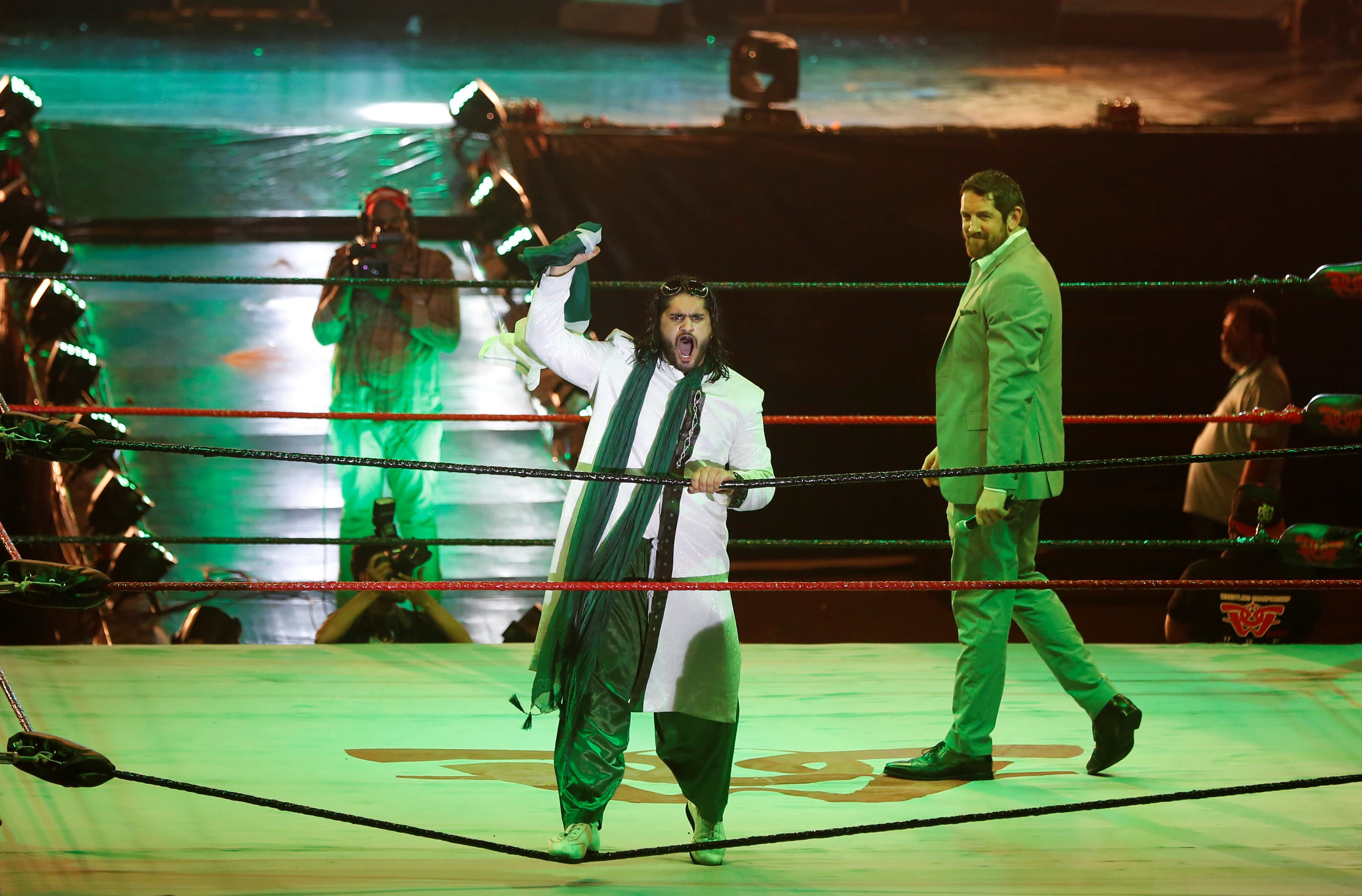Pakistani wrestler Baadshah Pehalwan Khan (C) holds a national flag as he reacts to the fans during the opening ceremony of the Pro Wrestling Entertainment show.
