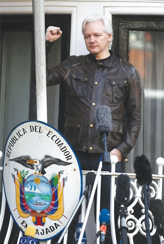 LONDON: Julian Assange raises his fist before addressing the media on the balcony of the Ecuador embassy on Friday.—AFP