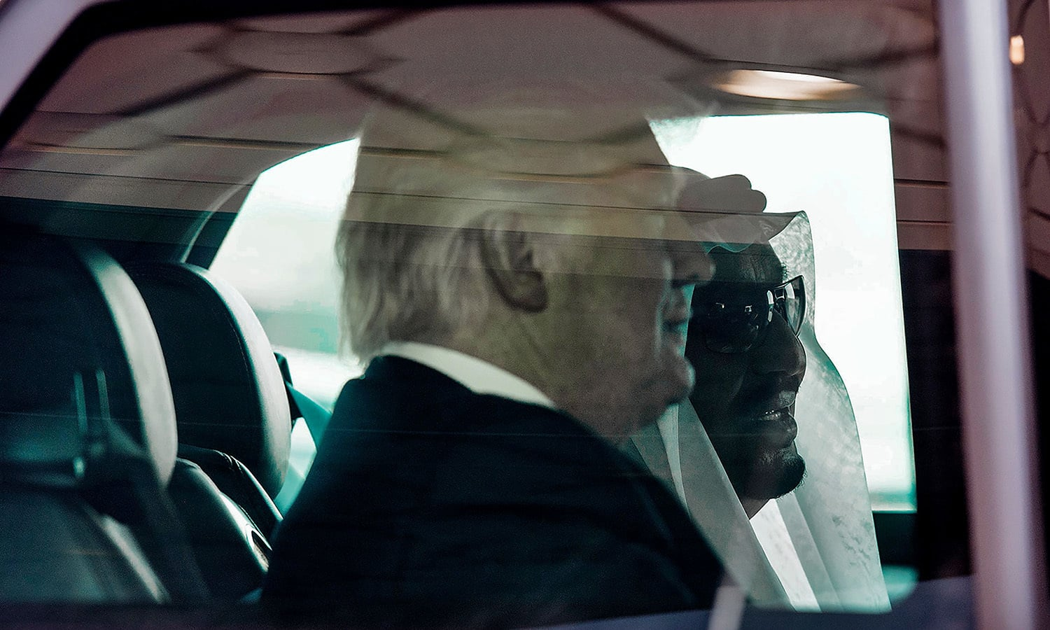President Trump rides in a car with Saudia Arabia's King Salman as they leave King Khalid International Airport. ─ AFP