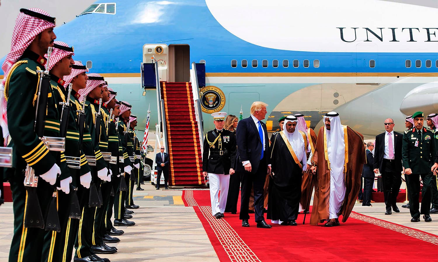 Trump and King Salman walk away from Air Force One. ─ AFP