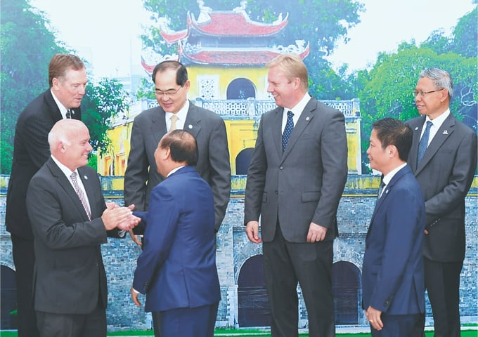 Vietnam's Prime Minister Nguyen Xuan Phuc (front C) shakes hands with US Trade Representative Robert Lighthizer as Peru's Foreign Trade Minister Eduardo Ferreyros (front L), Singapore's Trade Minister Lim Hng Kiang (back 2nd L), New Zealand's Trade Minister Todd McClay (back 2nd R), Malaysia's Trade Minister Mustapa Mohamed (back R), and Vietnam's Minister of Trade Tran Tuan Anh (front R) look on during a group photo session at the APEC Minister's Responsible For Trade meeting in Vietnam on May 20.—Reuters