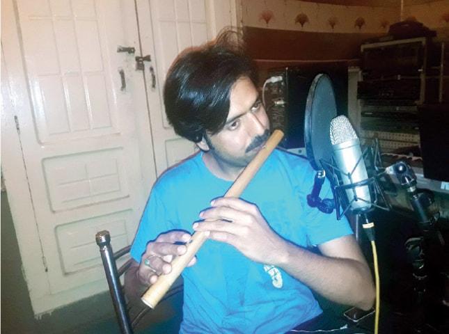 Shaukat Paniyal plays a flute at a private music studio in Peshawar. — Dawn