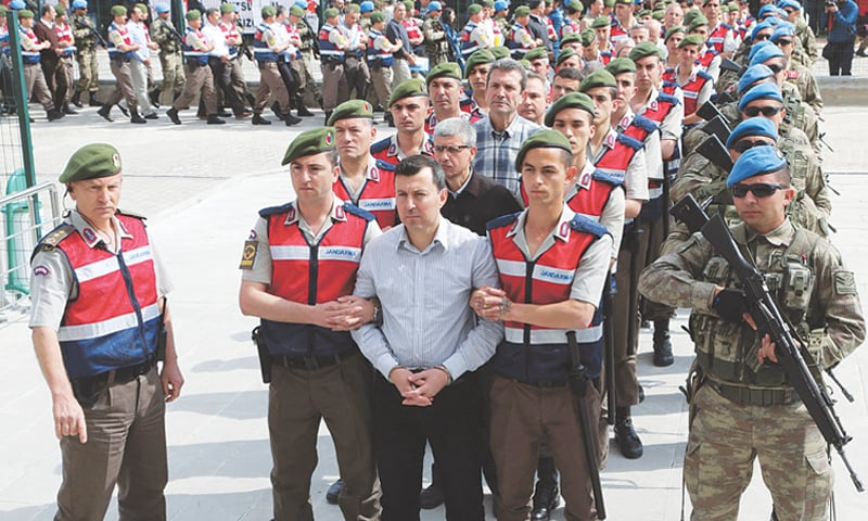 SINCAN: A soldier accused of being involved in the coup plot is accompanied by Turkish soldiers as they arrive at the court inside the Sincan prison, on the outskirts of Ankara, on Monday.—AFP