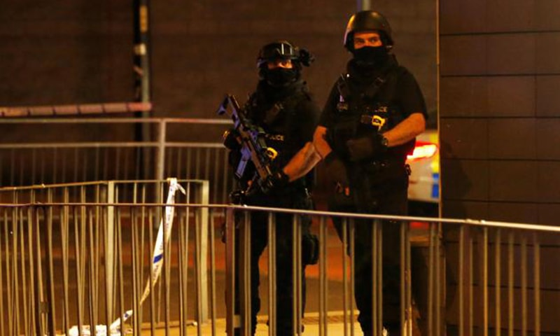 Armed police officers stand next to a police cordon outside the Manchester Arena, where U.S. singer Ariana Grande had been performing, in Manchester, northern England.  — Reuters