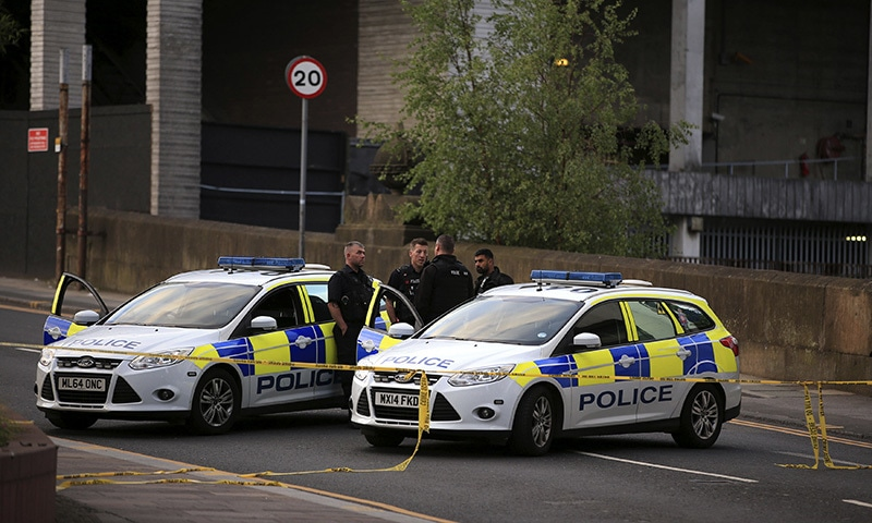 Police officers stand next to their vehicles near the Manchester Arena, May 23. ─AP.
