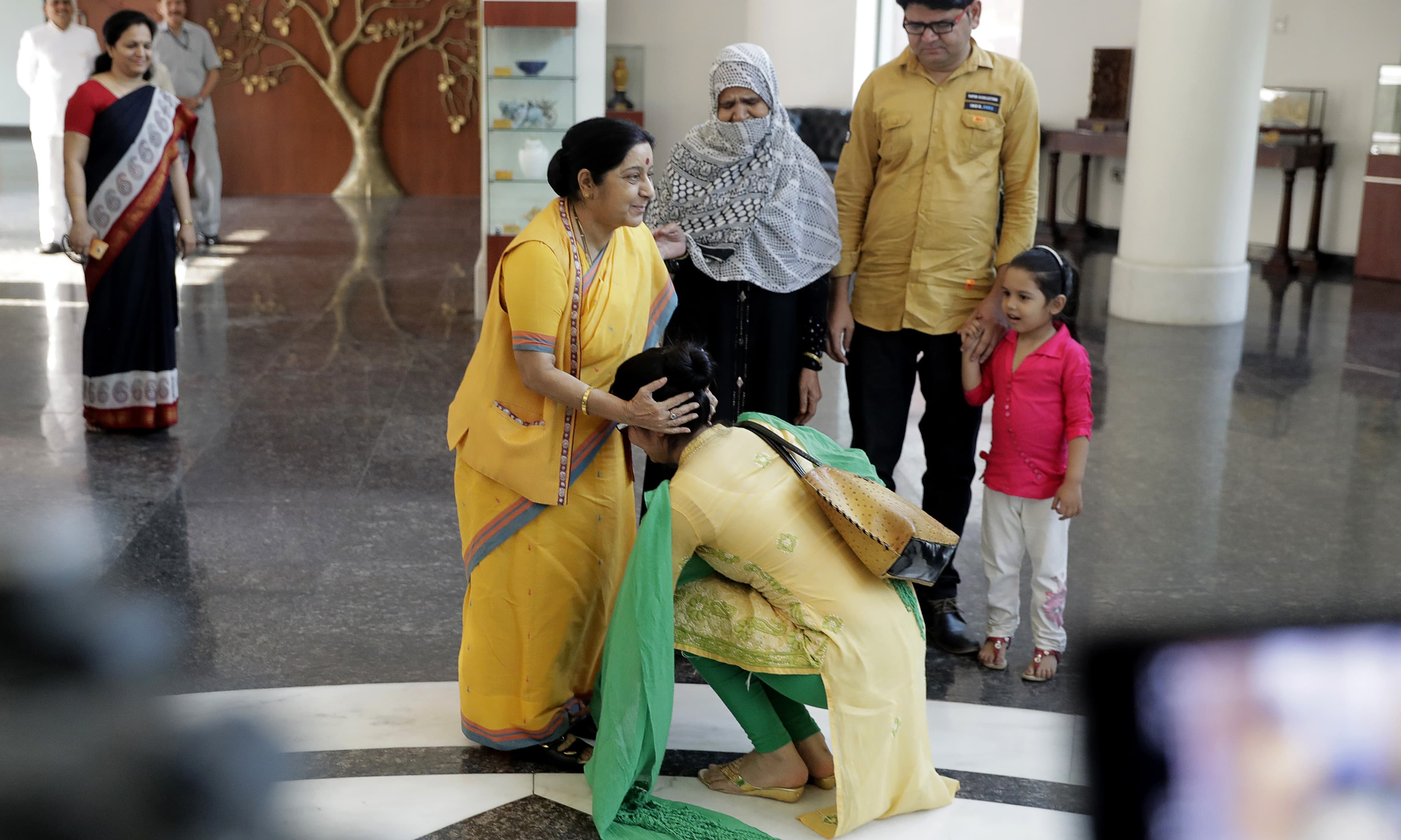 Uzma touches the feet of Sushma Swaraj as a mark of respect and gratitude. —AP