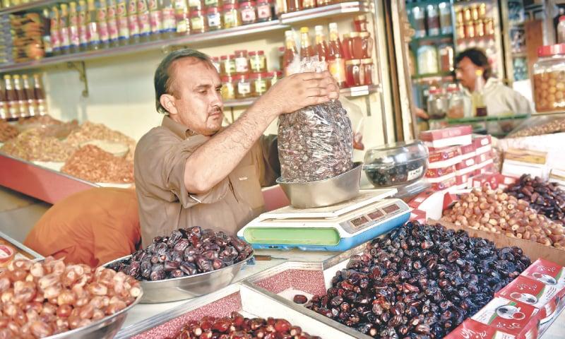 Naqeeb Khan preparing a big bag of dates for a customer. / Photos by Fahim Siddiqi / White Star