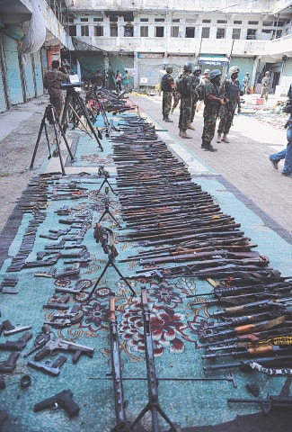 Soldiers stand by seized weapons in an empty bazaar during a military operation against militants in the main town of Miramshah in North Waziristan | AFP
