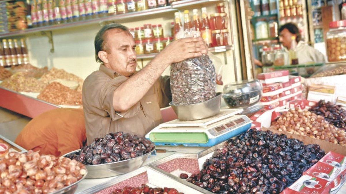Naqeeb Khan preparing a big bag of dates for a customer. / Photos by Fahim Siddiqi / White Star