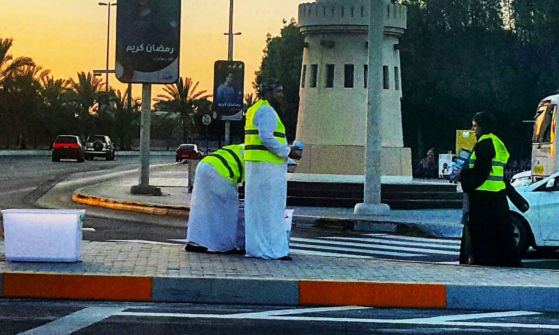 سڑک کے کنارے افطار بانٹنے کے لیے کھڑے رضاکار— تصویر صوفیہ کاشف