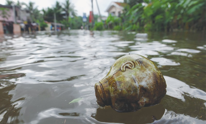 A doll head floats in a flooded lane in Dodangoda village, Kalutara, on Sunday. —AFP