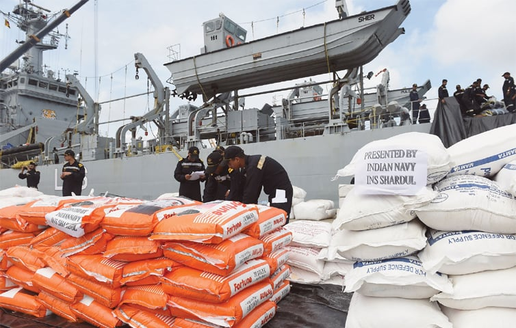 Indian Navy troops offload emergency supplies from an Indian ship at Colombo harbour.—AFP