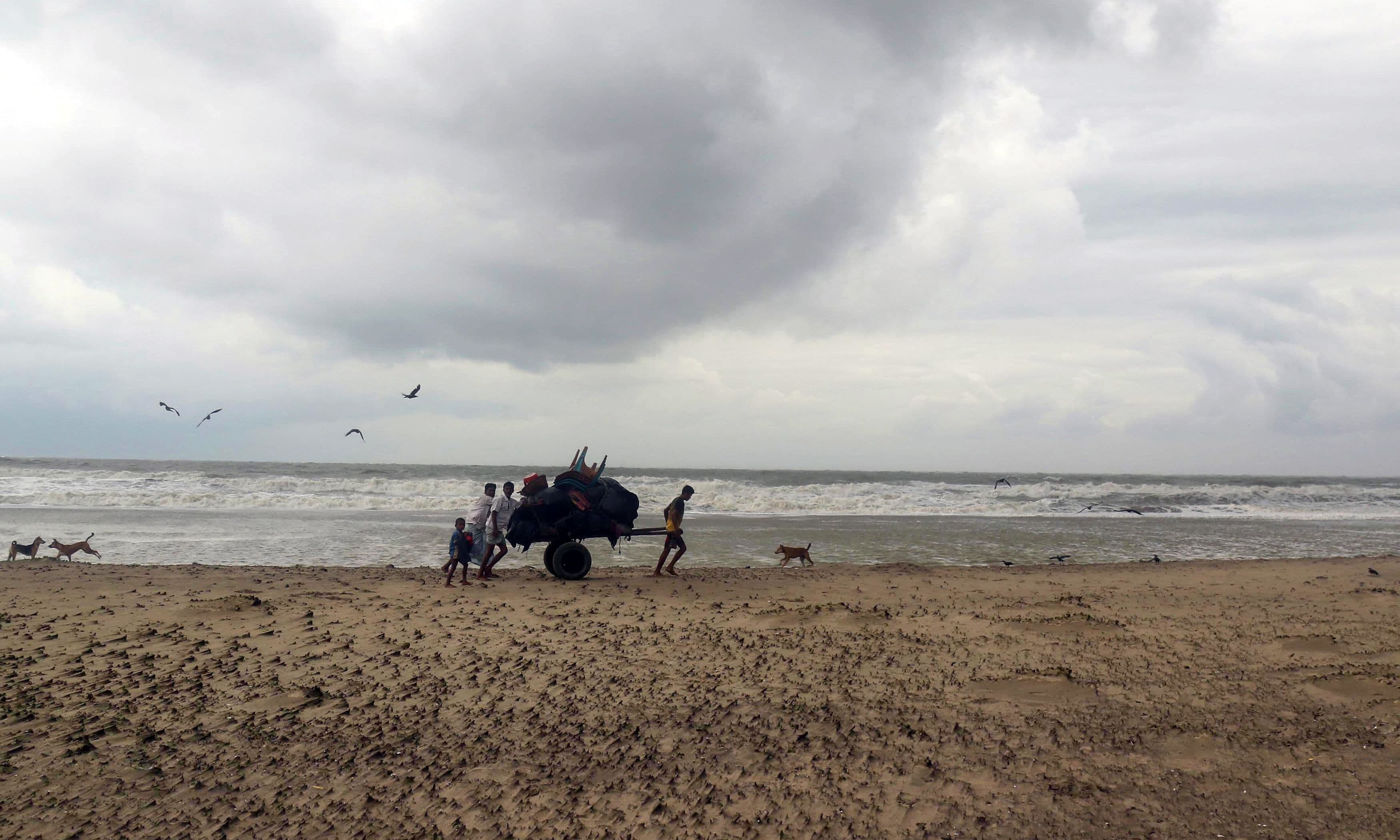 Bangladeshi villagers evacuate to cyclone shelters on the coast in Cox's Bazar district. —AFP