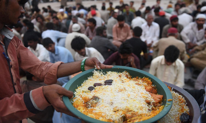 کراچی میں رضاکار روزہ داروں کو افطاری کے کھانا فراہم کرتے ہوئے—فوٹو: اے ایف پی