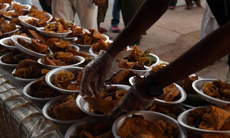 روڈ افطاری کے رضاکار ایسے روزہ داروں کو بھی افطاری کا سامان دیتے ہیں جو روڈ سے گزر رہے ہوتے ہیں—فوٹو: اے ایف پی