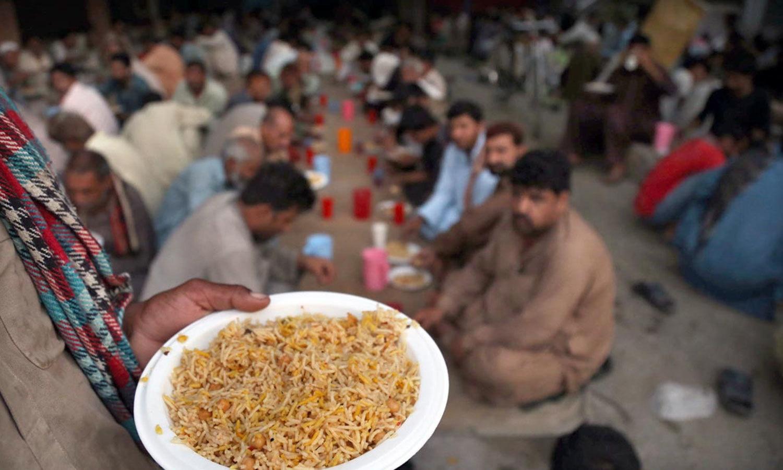 لاہور کے بادامی باغ میں لوگوں کو افطار کرایا جا رہا ہے—فوٹو: آن لائن