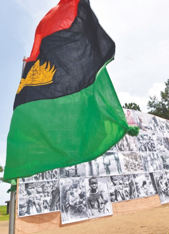 ABIDJAN: A Biafra flag flies next to the photos of Igbos who died during the 30-month civil war fifty years ago.—AFP